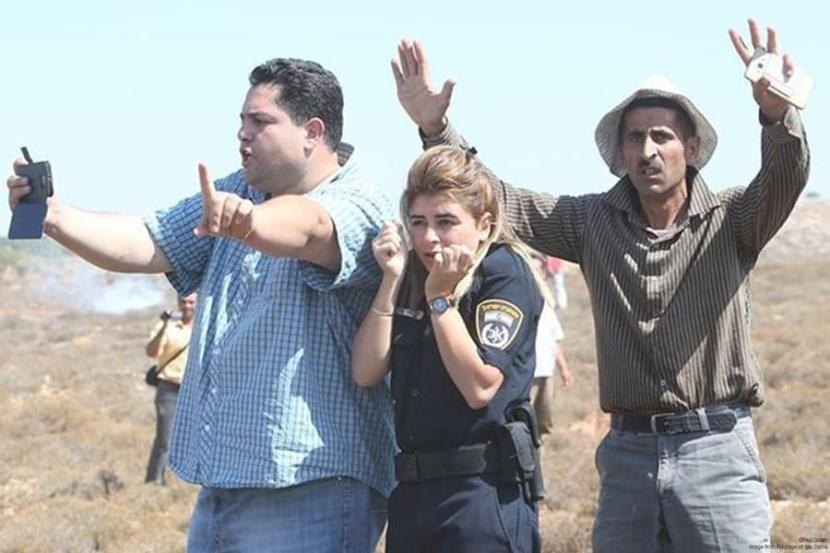 Palestinian nonviolent activists defending Israeli policewoman from Israeli settler attack at Esh Kodesh outpost, August 2015.